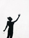 Ragazza che allunga la sua mano verso il cielo intorno sui precedenti bianchi della parete Immagine Stock