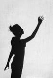 Ragazza che allunga la sua mano verso il cielo intorno sui precedenti della parete Immagini Stock