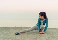 Ragazza che allunga le sue gambe sulla costa, wokout Immagini Stock