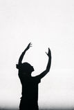 Ragazza che allunga le sue mani verso il cielo intorno sui precedenti bianchi della parete Fotografie Stock Libere da Diritti