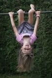 Ragazza che appende upside-down sul blocco per grafici di scalata Fotografia Stock