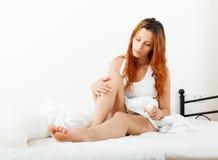 Ragazza che applica crema sulle gambe Fotografia Stock Libera da Diritti