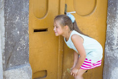 Ragazza che ascolta attraverso la porta arancio Immagine Stock