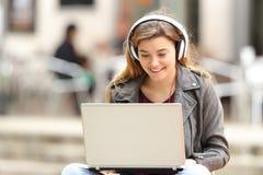 Ragazza che ascolta e che scarica musica dal computer portatile Fotografia Stock