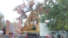 Ragazza che ascolta la musica in caffè moderno Il traffico della via è sulla riflessione della finestra stock footage