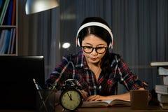 Ragazza che ascolta la musica mentre studiando Immagini Stock