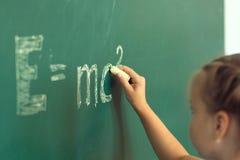 Ragazza che attinge formula e=mc2 della lavagna Istruzione e concetto della scuola Fotografie Stock Libere da Diritti