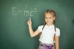 Ragazza che attinge formula e mc2 della lavagna Istruzione e concetto della scuola Fotografie Stock