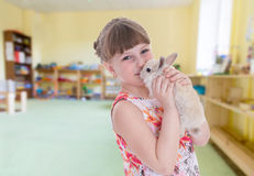Ragazza che bacia un coniglio fotografia stock