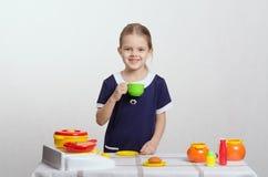 Ragazza che beve dalla tazza alla sua cucina Immagine Stock