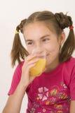 Ragazza che beve il succo di arancia I Immagini Stock Libere da Diritti