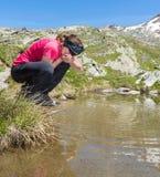 Ragazza che beve l'acqua pulita del lago Immagini Stock Libere da Diritti