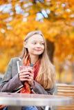 Ragazza che beve vino caldo in un caffè Fotografia Stock