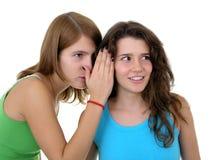 Ragazza che bisbiglia in orecchio del `s dell'amico fotografie stock