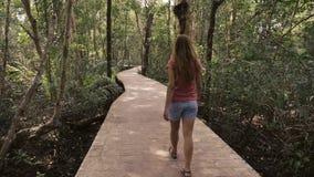 Ragazza che cammina al rallentatore nella foresta tropicale video d archivio