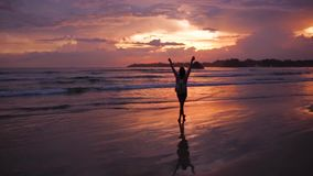 Ragazza che cammina al tramonto dall'oceano stock footage