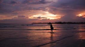 Ragazza che cammina al tramonto vicino all'oceano stock footage
