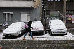 Ragazza che cammina attraverso la città nevosa Fotografia Stock