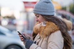 Ragazza che cammina e che manda un sms sullo smartphone nella via Immagine Stock