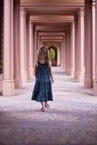 Ragazza che cammina giù il corridoio nel vecchio giardino del palazzo Immagini Stock