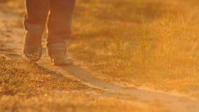 Ragazza che cammina giù la strada, gambe primo piano, tramonto video d archivio