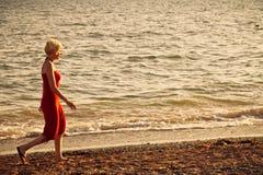 Ragazza che cammina lungo la spiaggia fotografie stock