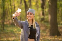 Ragazza che cammina nel legno e che fa un selfie immagine stock
