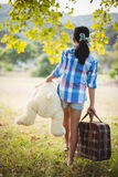 Ragazza che cammina nel parco con una valigia e un orsacchiotto Fotografie Stock Libere da Diritti