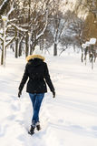 Ragazza che cammina nel parco della neve di inverno Immagini Stock Libere da Diritti