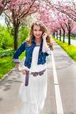 Ragazza che cammina nel parco di fioritura della molla Fotografia Stock Libera da Diritti