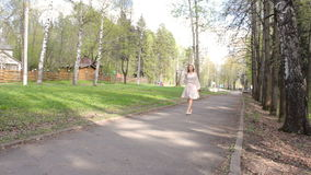 Ragazza che cammina nel parco tramite il vicolo stock footage