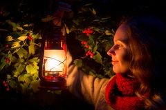 Ragazza che cammina nella foresta scura con la vecchia lanterna a disposizione Fotografia Stock
