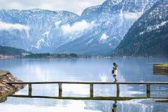 Ragazza che cammina su una piattaforma sopra un lago alpino Fotografie Stock