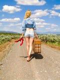 Ragazza che cammina su una strada non asfaltata con una valigia Fotografia Stock