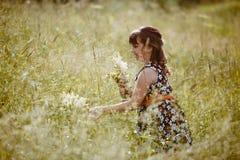 Ragazza che cammina sul campo accanto ai wildflowers immagini stock libere da diritti