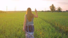 Ragazza che cammina sul campo al tramonto e che mostra il dito medio Movimento lento video d archivio