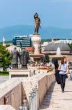 Ragazza che cammina sul ponte, sullo strumento musicale di trasporto, sulle sculture famose come Philip Second di Macedon o sui s fotografia stock