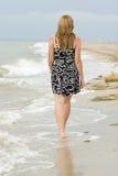 Ragazza che cammina sulla sabbia. Immagine Stock