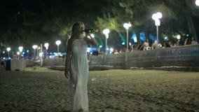 Ragazza che cammina sulla spiaggia Vino bevente Località di soggiorno di notte Donna in vestito bianco stock footage