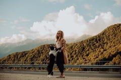 Ragazza che cammina sulla strada con il suo cane nelle montagne immagine stock