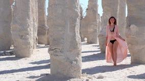 Ragazza che cammina vicino ad una colonna della sabbia stock footage