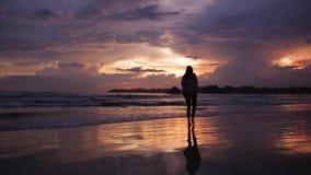 Ragazza che cammina vicino all'oceano al tramonto archivi video