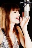 Ragazza che canta al microfono in uno studio Immagine Stock Libera da Diritti