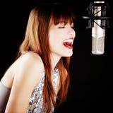 Ragazza che canta al microfono in uno studio Fotografia Stock Libera da Diritti