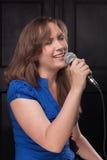 Ragazza che canta al microfono in uno studio Fotografia Stock