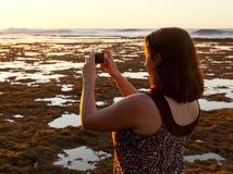 Ragazza che cattura foto del tramonto sul telefono fotografie stock libere da diritti