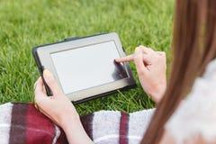 Ragazza che cerca informazioni sul web tramite compressa in aria fresca Fotografia Stock