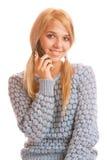 Ragazza che comunica sul sul suoi telefono e sorridere delle cellule Fotografia Stock