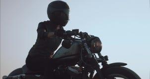 Ragazza che conduce un motociclo contro il cielo su una vista laterale della strada della ghiaia stock footage
