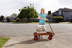 Ragazza che consegna i giornali con un vagone nella sua vicinanza Fotografie Stock Libere da Diritti
